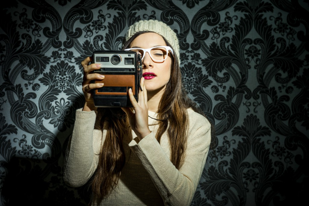 Fashionable girl with old camera