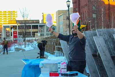Student distributing cotton candy at Winter Carnival on the Memorial Union Terrace
